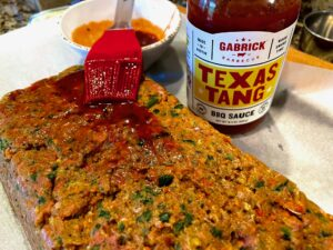 basting texas tang bbq sauce on meatloaf